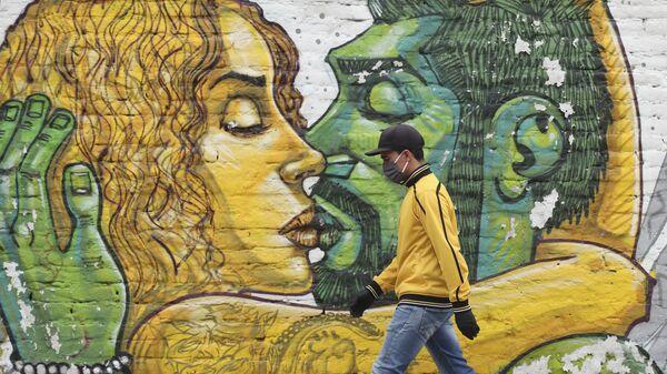 Un hombre en mascarilla pasa al lado de un muro con graffiti en Quito - Sputnik Mundo