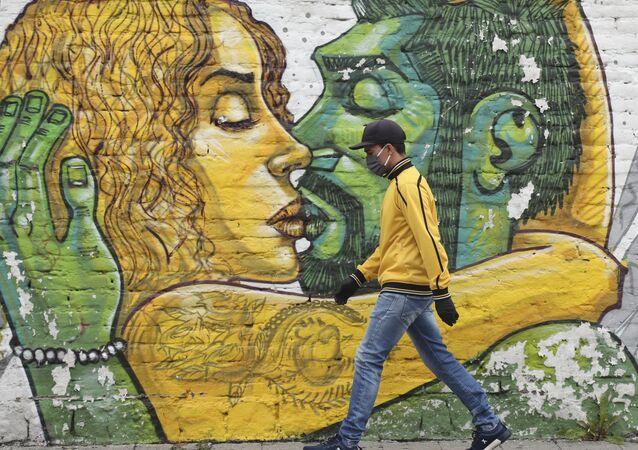Un hombre en mascarilla pasa al lado de un muro con graffiti en Quito