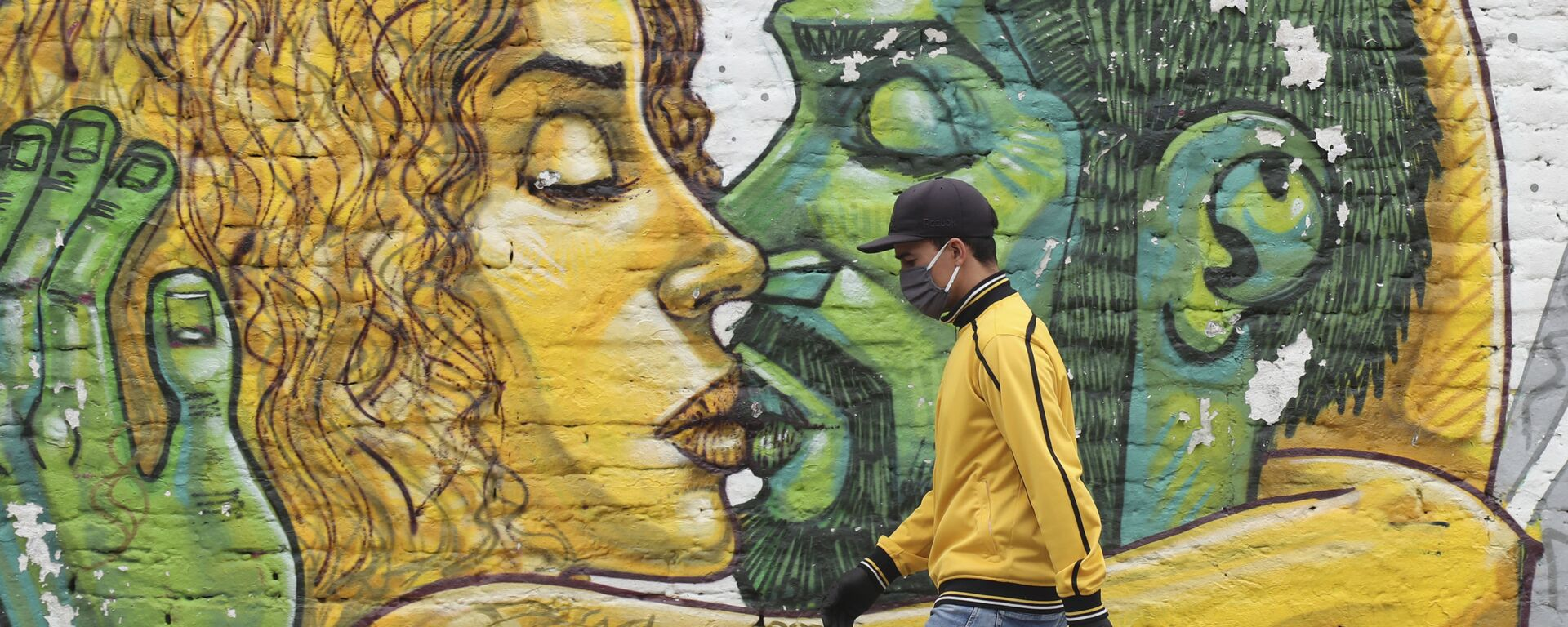 Un hombre en mascarilla pasa al lado de un muro con graffiti en Quito - Sputnik Mundo, 1920, 10.04.2021