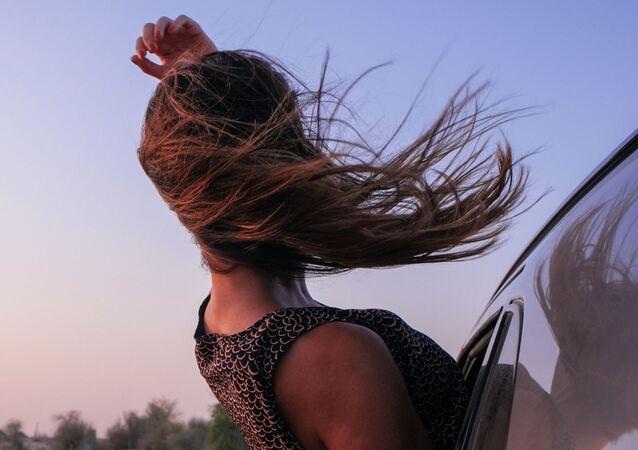 Una joven se asoma por la ventanilla de un coche