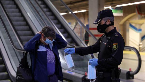 Un policía entrega una mascarilla a una mujer en el metro de Madrid - Sputnik Mundo