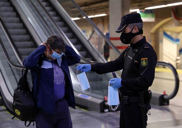 Un policía entrega una mascarilla a una mujer en el metro de Madrid