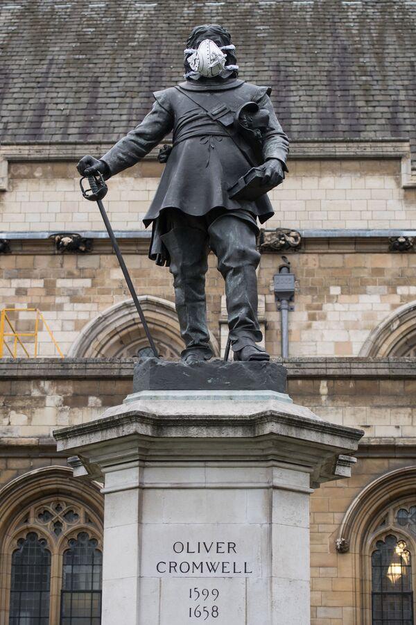 La estatua de Oliver Cromwell, que está justo fuera del Parlamento en el centro de Londres, lleva una mascarilla - Sputnik Mundo