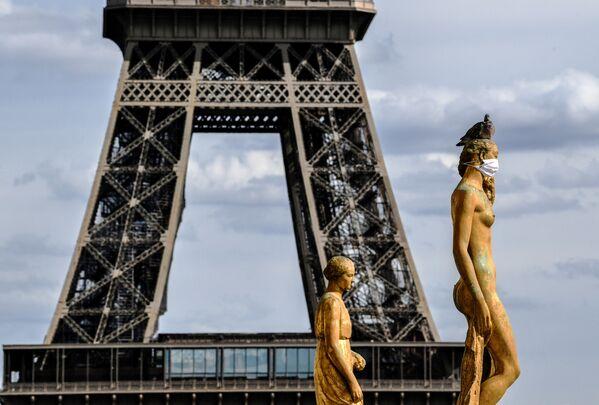 La Torre Eiffel se ve detrás de las estatuas de bronce con mascarillas, en el Parvis des Droits de l'Homme, en Francia - Sputnik Mundo