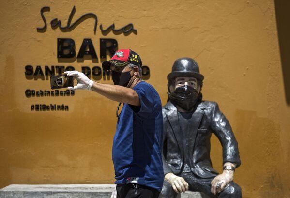 Un hombre con barbijo se toma una selfie en la escultura del cantante español Joaquín Sabina, que también lleva una mascarilla, en Santo Domingo, República Dominicana - Sputnik Mundo