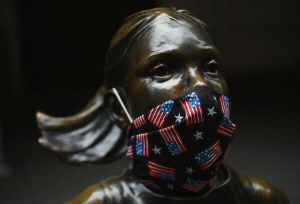 La famosa estatua 'Fearless Girl', que está en Wall Street, lleva una máscarilla con pequeñas banderas estadounidenses  - Sputnik Mundo