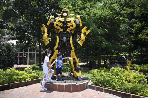 Un niño juega con la estatua del transformer de la película Bumblebee en la Ciudad de Guatemala, ambos llevan máscaras  - Sputnik Mundo