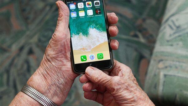 Un teléfono móvil en manos de una persona mayor  - Sputnik Mundo