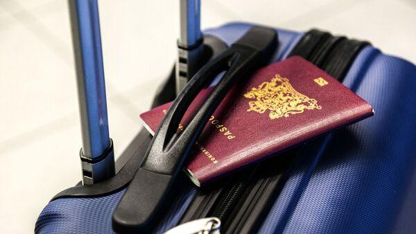Un pasaporte y una maleta (imagen referencial) - Sputnik Mundo