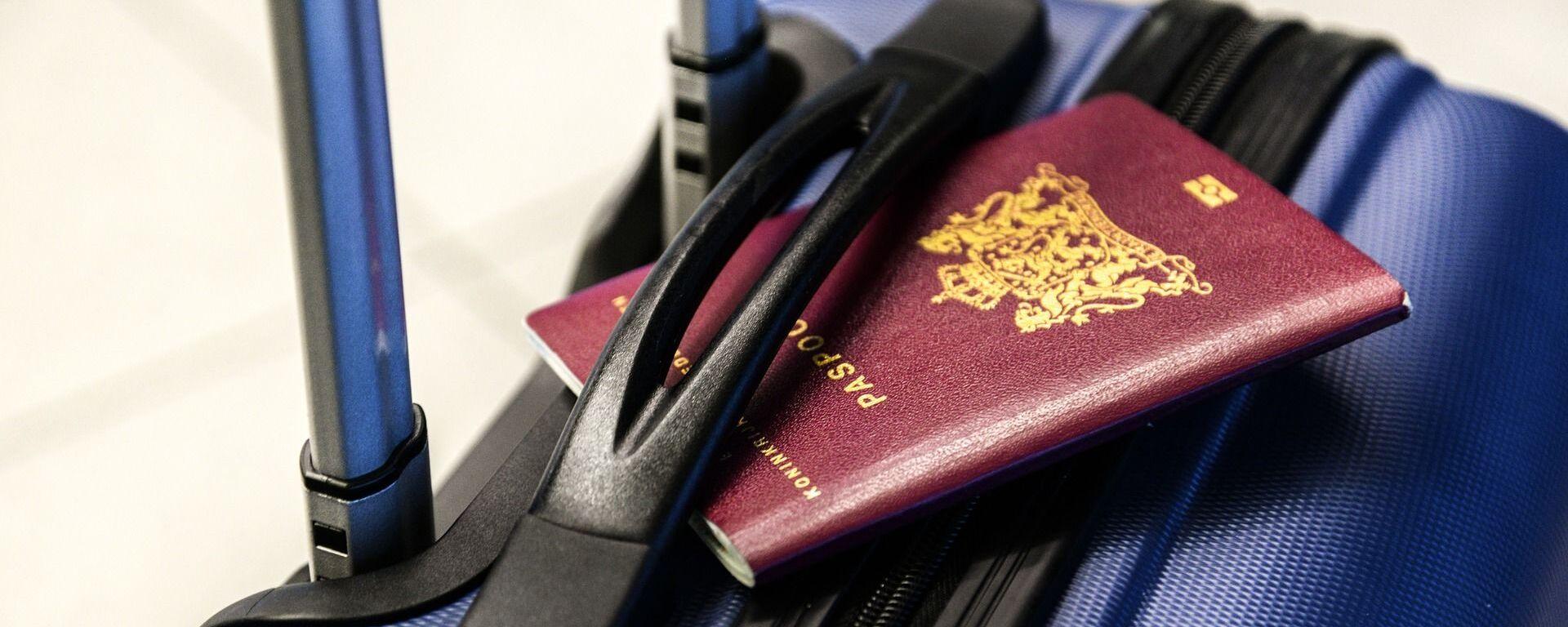 Un pasaporte y una maleta (imagen referencial) - Sputnik Mundo, 1920, 19.08.2021