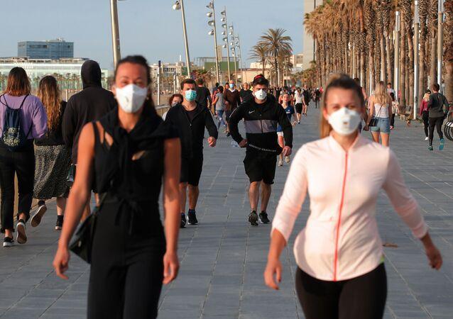 Caminantes en el paseo marítimo de Barcelona durante la desescalada