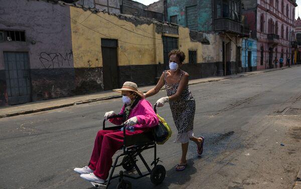 Flor Vaso empuja a su madre Carmen Reyes, de 84 años, en una silla de ruedas después de que fue vacuna contra la Influenca, durante el estado de emergencia decretado por el gobierno. Lima, Perú.  - Sputnik Mundo