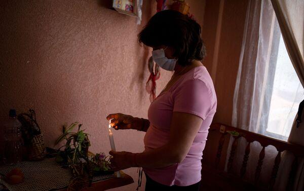 Marta Jaque enciende una vela a los santos en su altar casero durante el domingo de pascua. Quito, Ecuador.  - Sputnik Mundo
