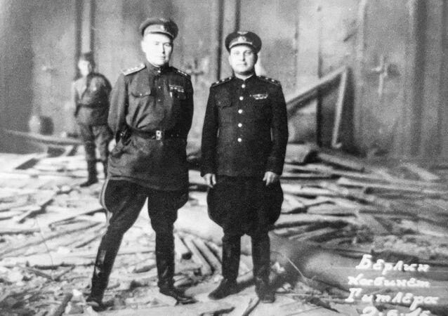 El comandante del 4 Ejército aéreo de la URSS, Konstantín Vershinin, (izquierda) posa en el despacho destruido de Hitler