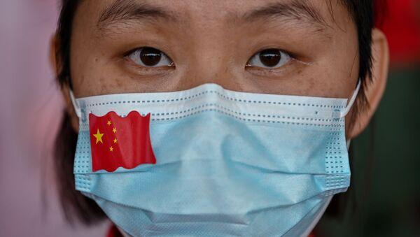 Una mujer con una mascarilla con la bandera de China - Sputnik Mundo