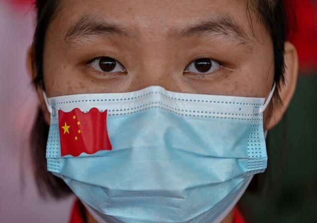 Una mujer con una mascarilla con la bandera de China