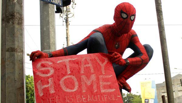 Un voluntario disfrazado de Spiderman tratando de evitar el contagio por coronavirus - Sputnik Mundo