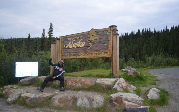 El MotoNauta en Alcan, en el cartel de bienvenida que está al salir de los territorios del norte de Canadá y entrar a Alaska, en la frontera con Yukon - Sputnik Mundo