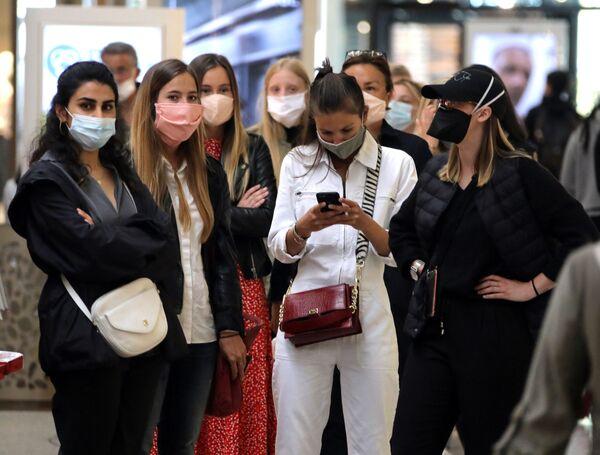 Девушки в масках во время открытия магазина после облегчения карантинных мер во Франции  - Sputnik Mundo