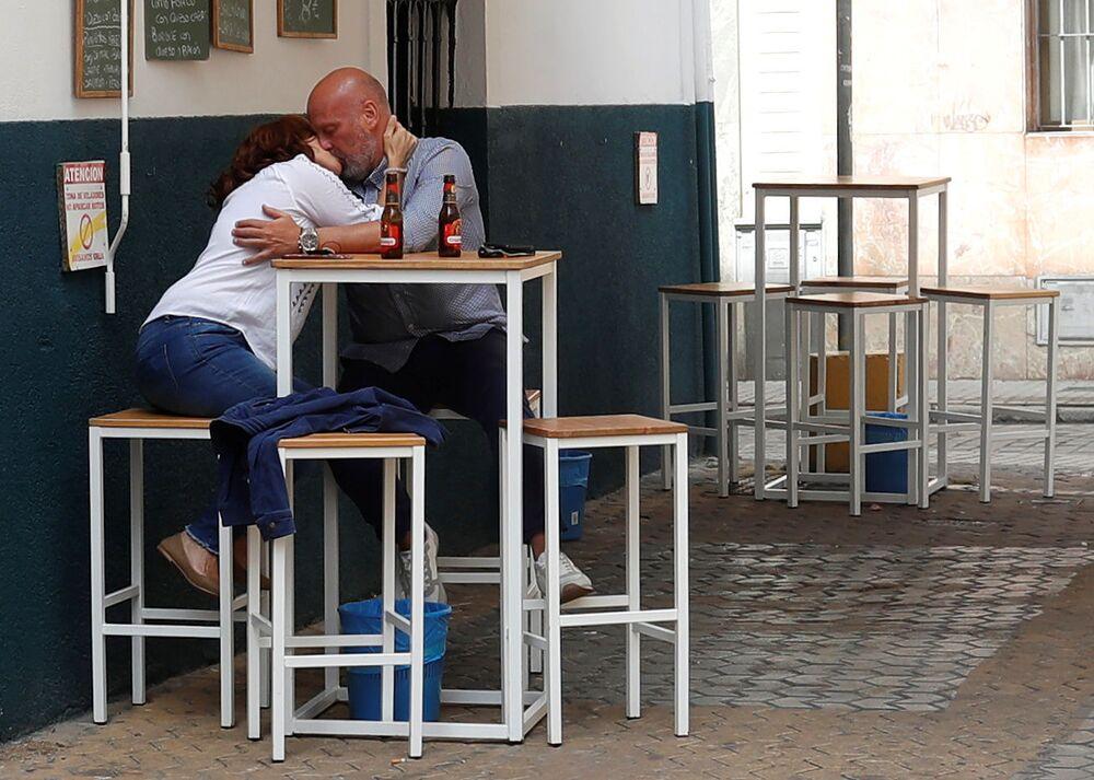La mayoría de las regiones de España también está volviendo a la vida normal. La primera fase de vuelta a la normalidad de un total de cinco ha comenzado. Los bares podrán abrir terrazas, pero no más del 50% de los asientos pueden estar ocupados. Se abrirán tiendas de menos de 400 metros cuadrados, cines, teatros e iglesias, siempre que no haya más de un tercio del número habitual de visitantes.   A los españoles se les permite reunirse con amigos y familiares en grupos de no más de 10 personas y caminar por la calle a una distancia de dos metros. Sin embargo, no se les permite salir de su municipio sin un permiso especial. En la foto: una pareja se besa en un bar de Sevilla.