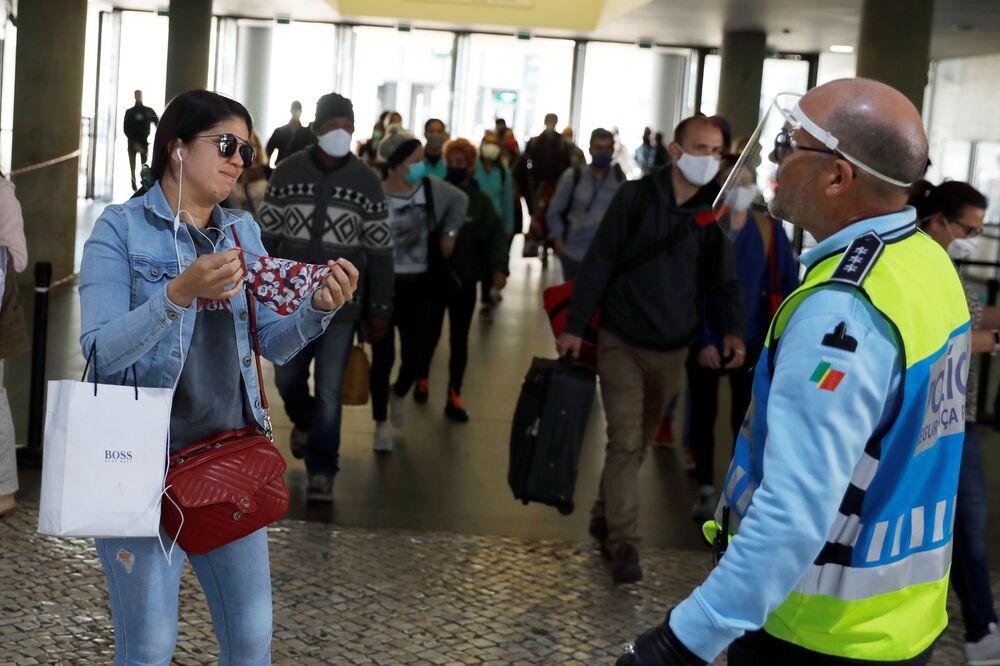 El uso de una mascarilla en los lugares públicos es obligatorio en casi todos los países. En la foto: un policía le obliga a una pasajera del metro en Lisboa (Portugal) a ponerse una mascarilla.