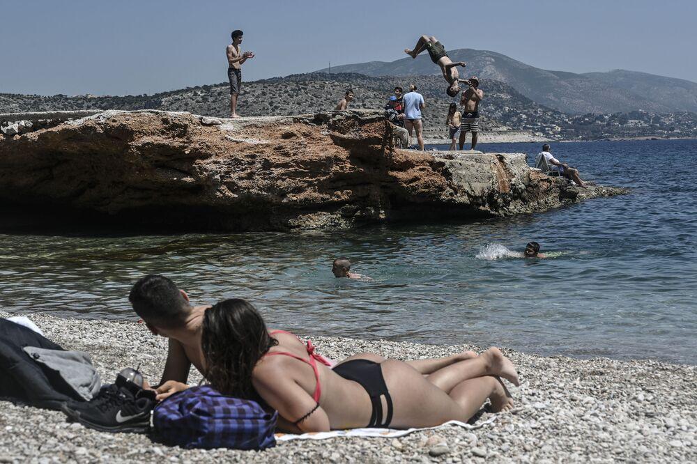 Varias personas toman el sol en una playa de Atenas (Grecia).