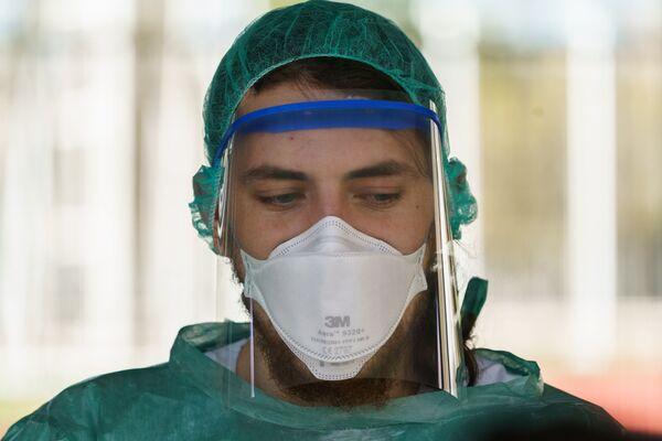 A healthcare worker dressed in protective gear  - Sputnik Mundo