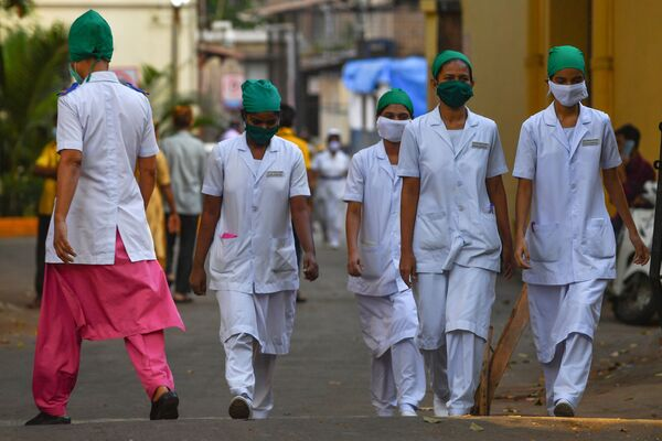 A nurse (L) arrives as others leave at the end of their shift at the King Edward Memorial (KEM) hospital in Mumbai - Sputnik Mundo