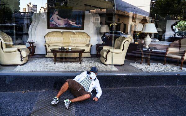 Hombre sin hogar frente a un negocio de diseño de interiores en pleno aislamiento obligatorio. Buenos Aires, Argentina.  - Sputnik Mundo