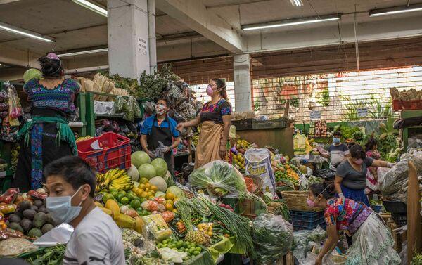 Vendedores protegidos con tapabocas organizando la mercadería en un mercado de frutas local. Ciudad de Guatemala, Guatemala. - Sputnik Mundo