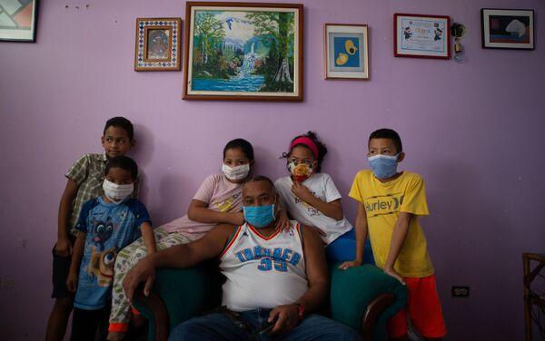 Un grupo de niños posan junto a su padre para un retrato en un departamento en La Lira, un vecindario en el área de Petare. Caracas, Venezuela.   - Sputnik Mundo