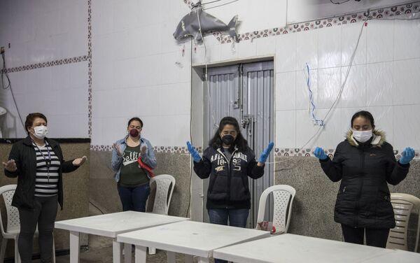 Un grupo de mujeres, distanciadas entre sí, rezan antes de recibir folletos de alimentos del grupo católico Amigos Misión Colombia. Bogotá, Colombia.  - Sputnik Mundo