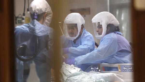 Médicos atienden paciente con coronavirus - Sputnik Mundo