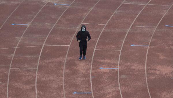 Un vecino de Wuhan corre con mascarilla - Sputnik Mundo