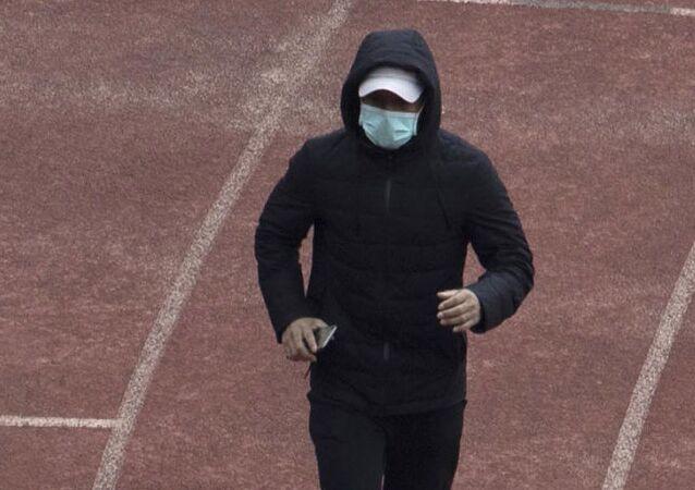 Un vecino de Wuhan corre con mascarilla