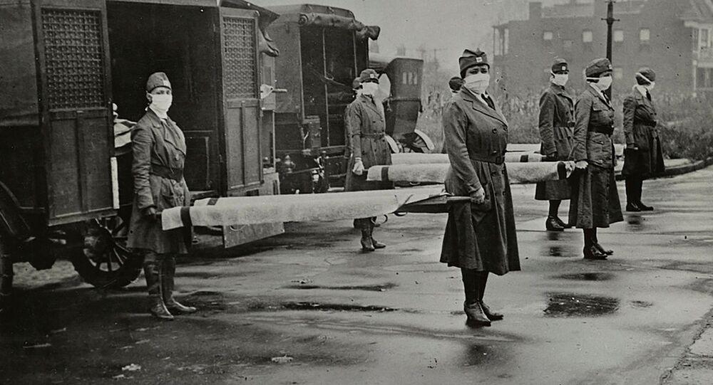 Mujeres con mascarillas sostienen camillas cerca de las ambulancias durante la pandemia de la gripe española en EEUU