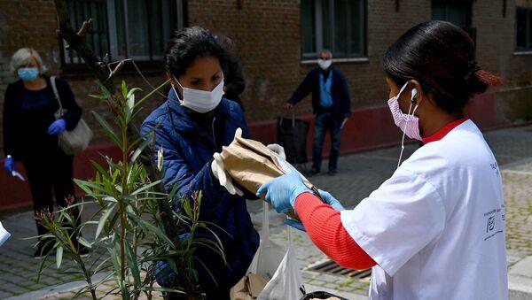 Mujer recibiendo una bolsa de alimentos en el barrio de Puente de Vallecas (Madrid) - Sputnik Mundo