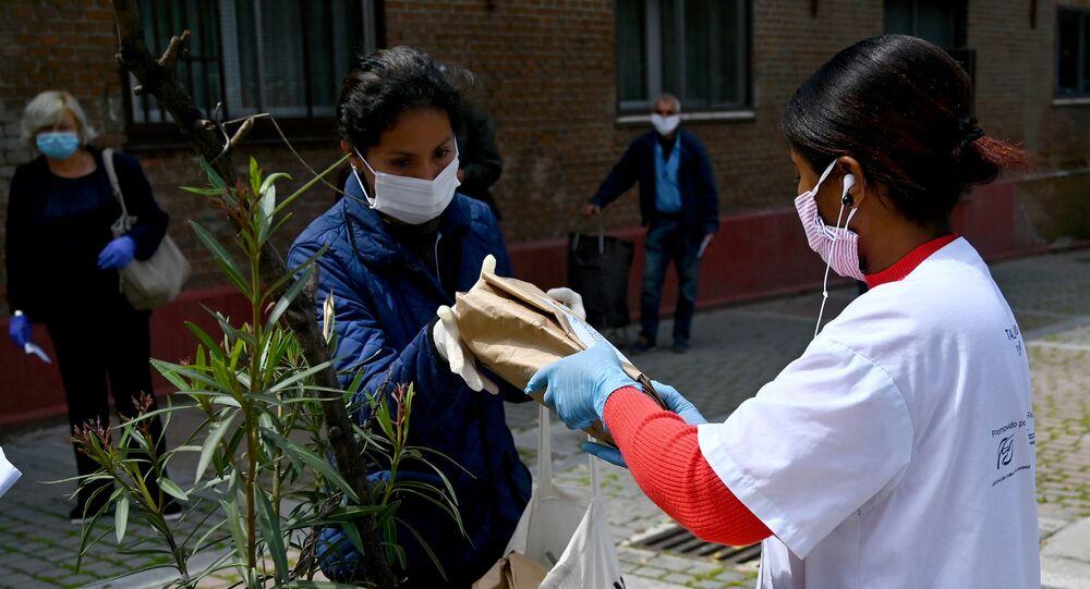 Mujer recibiendo una bolsa de alimentos en el barrio de Puente de Vallecas (Madrid)
