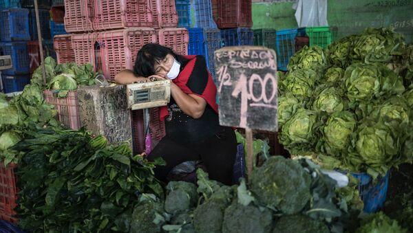Kathy Velázquez, usando una mascarilla protectora como precaución contra el coronavirus, toma una siesta en su puesto de verduras mientras espera a los clientes en Lima. - Sputnik Mundo