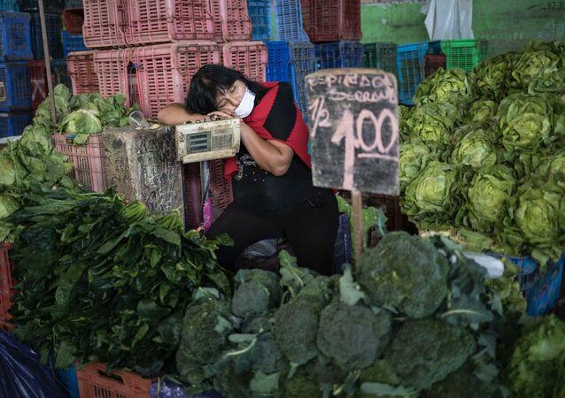 Kathy Velázquez, usando una mascarilla protectora como precaución contra el coronavirus, toma una siesta en su puesto de verduras mientras espera a los clientes en Lima.