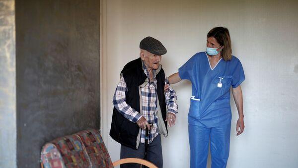 Una enfermera ayuda a un anciano en Francia - Sputnik Mundo