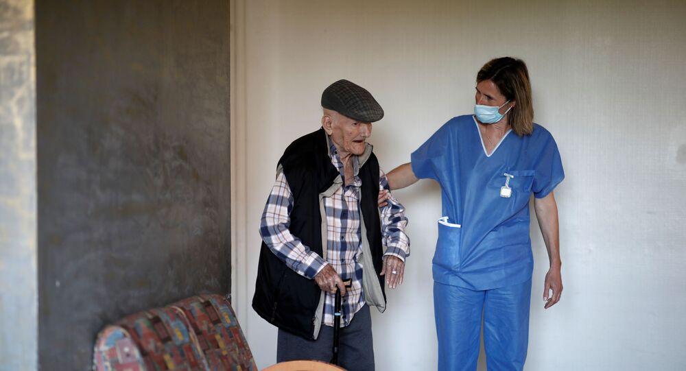 Una enfermera ayuda a un anciano en Francia (imagen referencial)