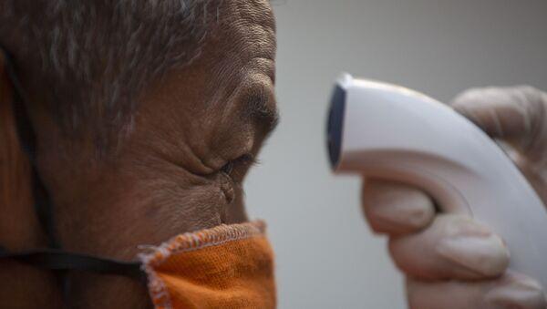 Un hombre con mascarilla haciendo una prueba por coronavirus - Sputnik Mundo