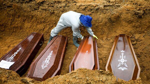 Un sepulturero trabaja durante un entierro masivo de personas que fallecieron debido al COVID-19 en Brasil - Sputnik Mundo
