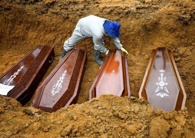 Un sepulturero trabaja durante un entierro masivo de personas que fallecieron debido al COVID-19 en Brasil