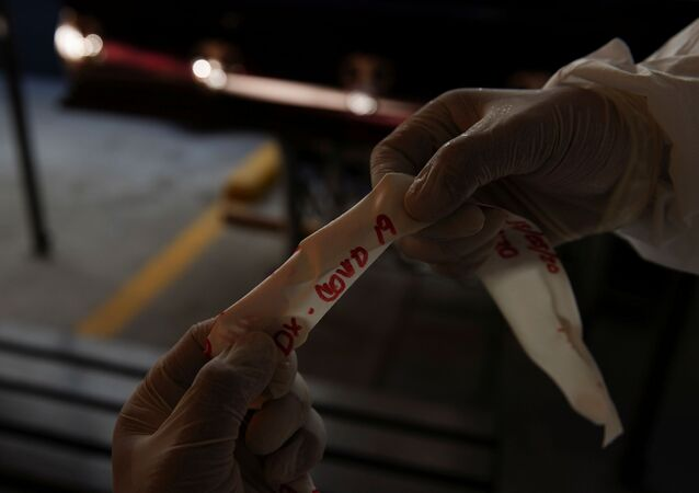 Un trabajador de una funeraria sostiene la cinta que dice COVID-19