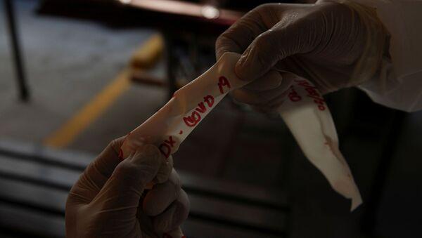 Un trabajador de una funeraria sostiene la cinta que dice COVID-19 - Sputnik Mundo