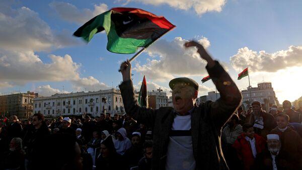 Un hombre con la bandera de Libia - Sputnik Mundo