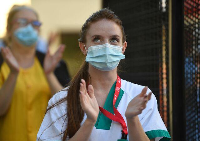 Sanitaria aplaudiendo en el Hospital Gregorio Marañón de Madrid