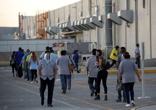 Trabajadores del fabricante estadounidense de autopartes Aptiv Plc llegan a la planta, en Ciudad Juárez, México, el 18 de mayo de 2020